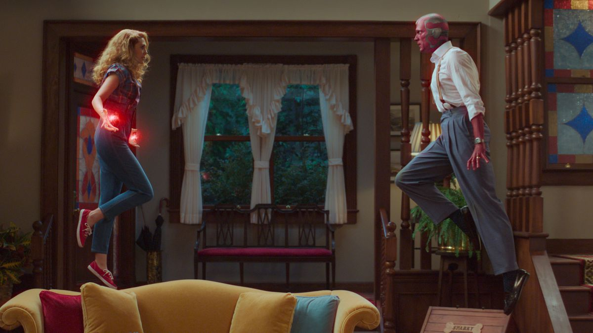 Wanda and Vision face off in their living room, using their powers to fly at each other above the sofa.