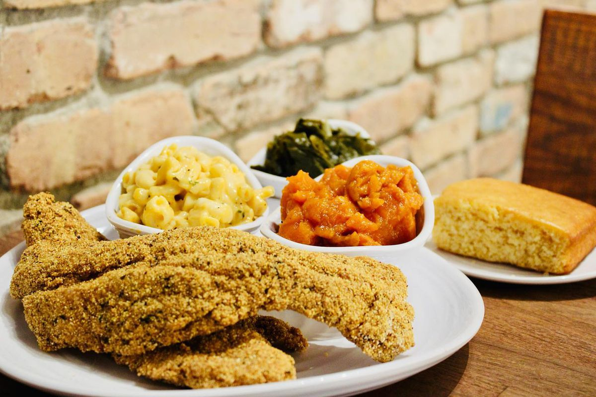 a plate of fried catfish, mac and cheese, mashed sweet potatoes, mustard greens and a slice of cornbread