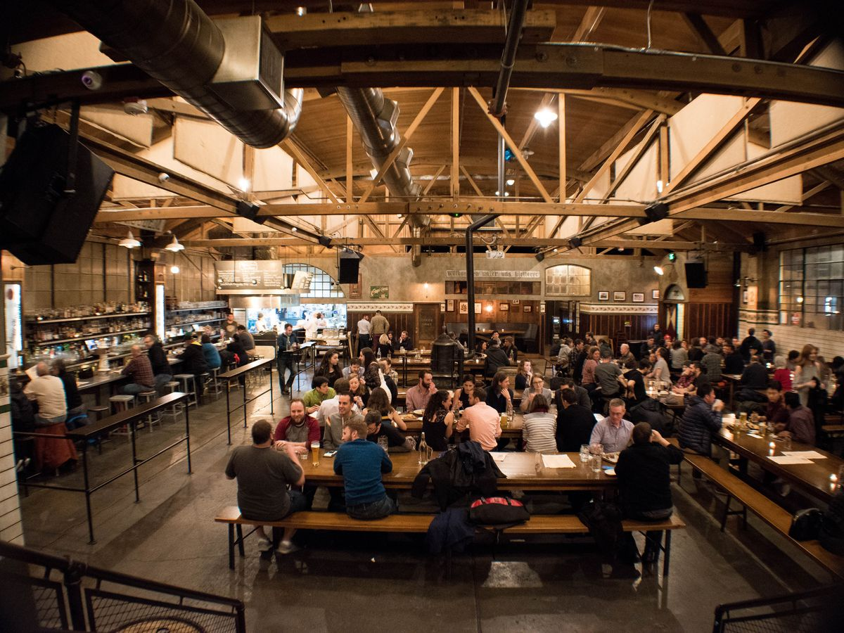 The large interior of Queen Anne Beerhall in Lower Queen Anne, with wood rafters and long communal tables.
