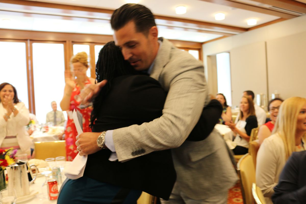 Vincent Gassetto, the principal M.S. 343, hugs a staff member after winning the Teaching Matters prize in July 2017.