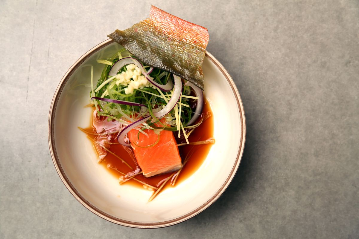 An overhead photograph of a bowl of poached fish, topped with thin green vegetables and dried fish skin