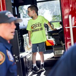 Liam Hancock, 6, checks out the cab of one of the Salt Lake City Fire Department's two new ladder trucks at Smith's Ballpark in Salt Lake City on Tuesday, June 27, 2017.