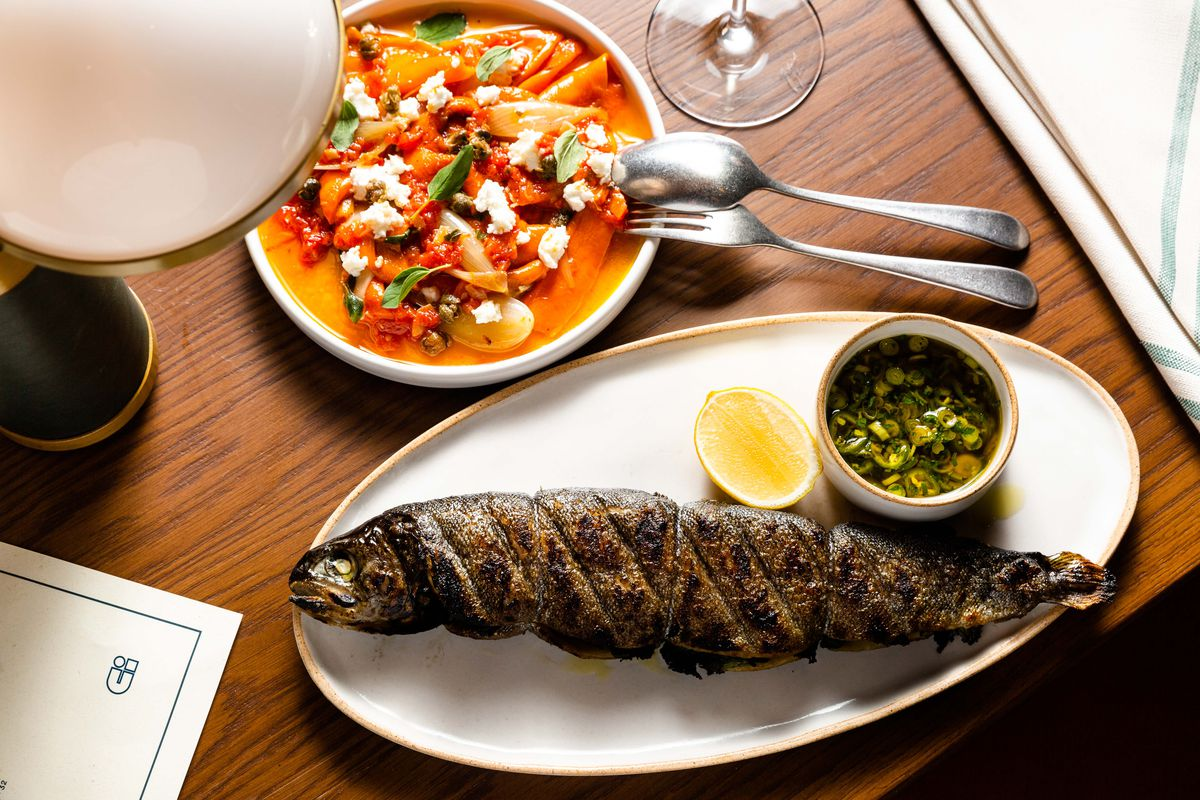 A table is set with two dishes, one with marinated and charred red and orange peppers; and another with a whole trout and side cup of dressing and half of a lemon.