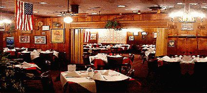 A dining room with retro wood paneling, vinyl booths, and tables draped in white tablecloths