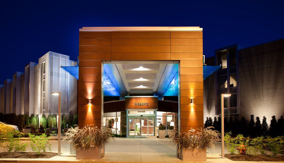 The wood paneled front entrance at night for Webers, a mid-century hotel.