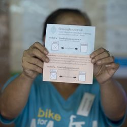 A volunteer holds a voter ballot indicating 'Yes' at a polling station on August 7, 2016 in Bangkok, Thailand.