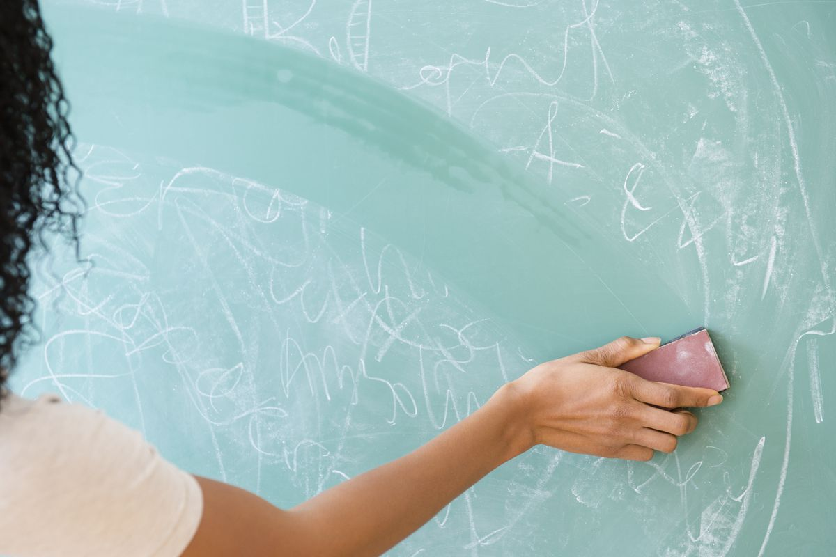 Teacher wiping a board clean with an eraser.
