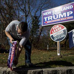Rhode Island entrepreneur Keith Lambert puts up Donald Trump flags outside of his store in Bellingham, Mass., Saturday, Nov. 9, 2019.