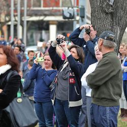 Thousands of people watch, some from rooftops, as they document events as workers place an Angel Moroni statue atop the Provo City Center Temple, Monday, March 31, 2014, in Provo.
