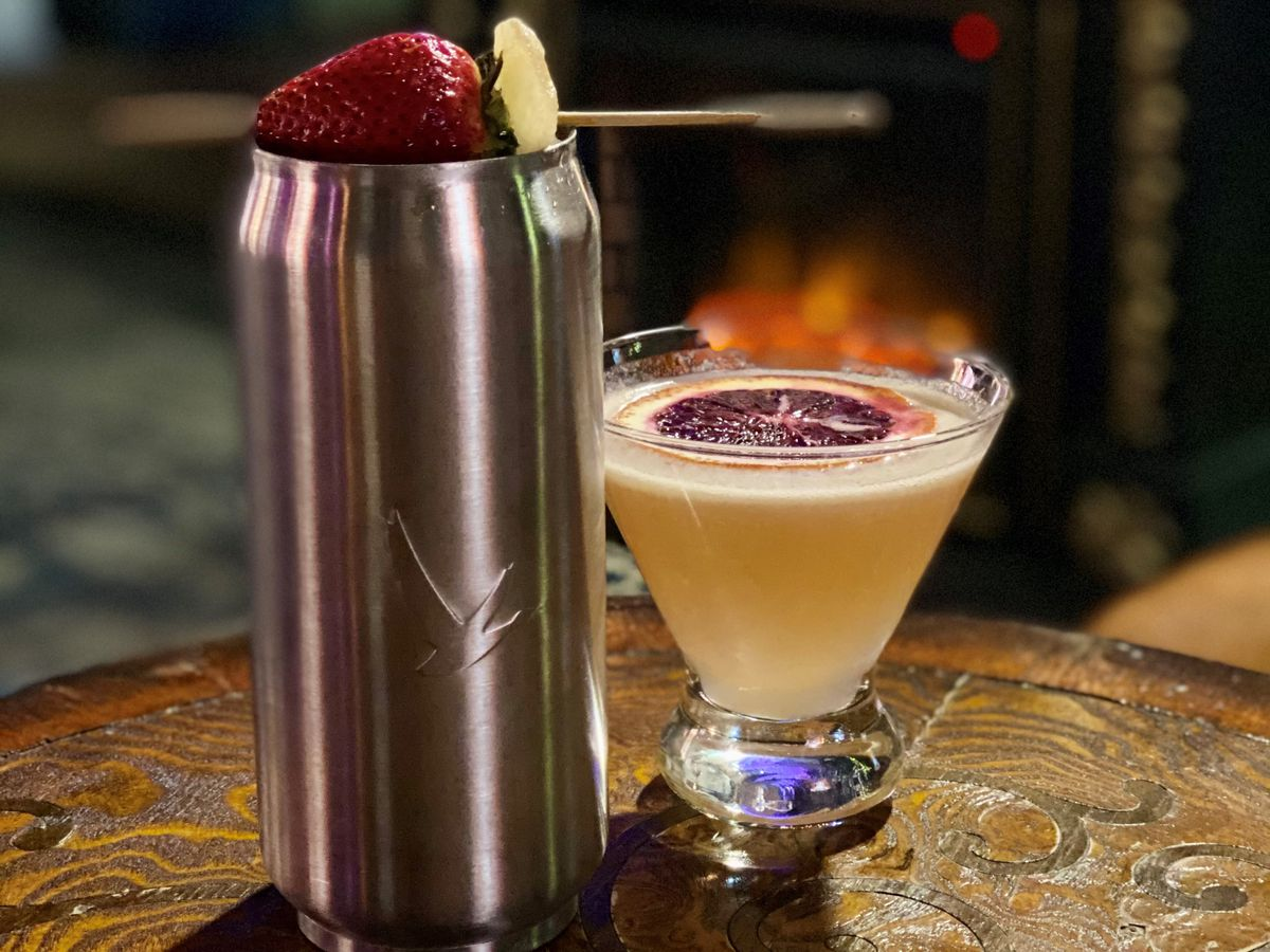 A cocktail at The Coppermine, in a short glass with a slice of blood orange sitting on the top. To the left is a tall silver can with a strawberry on top.
