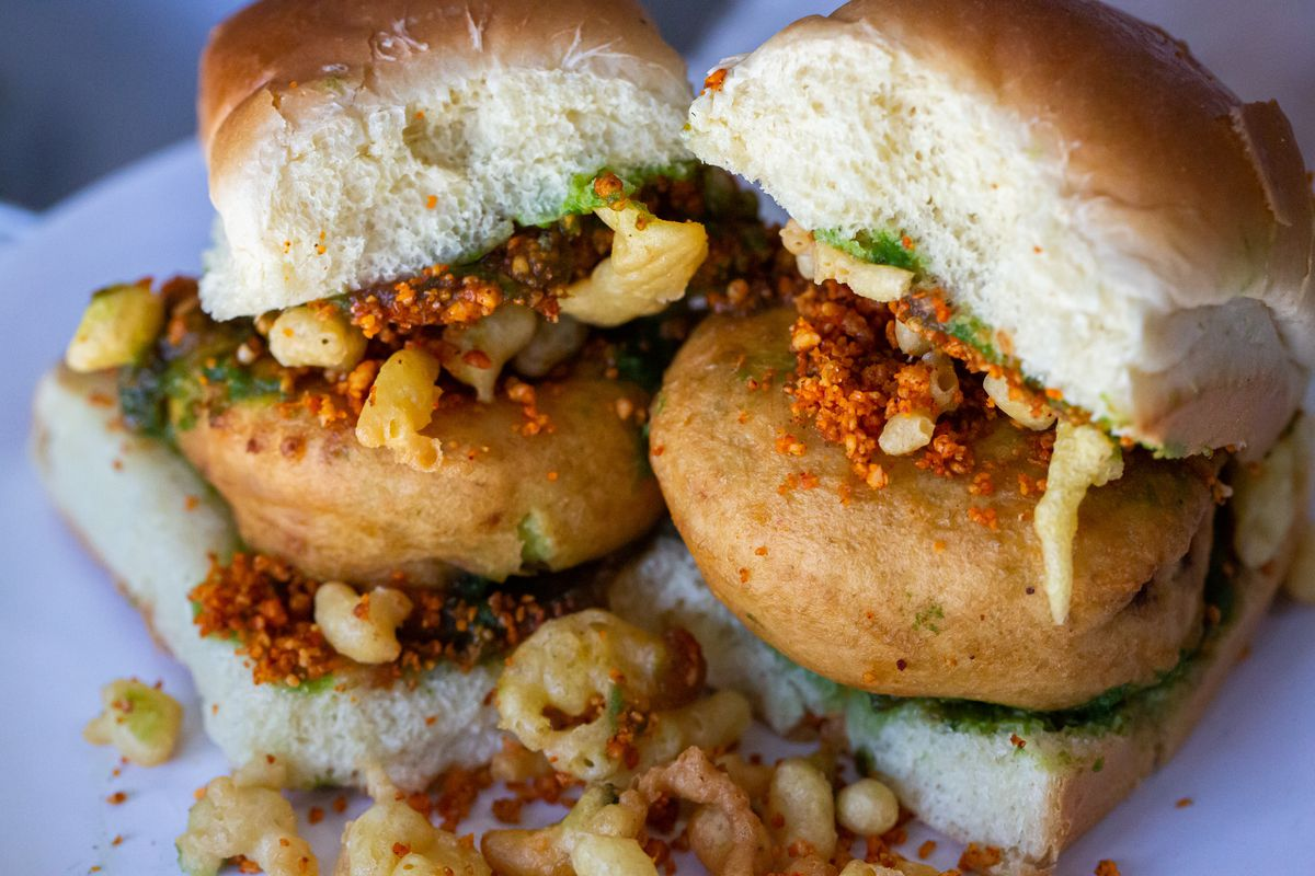 Two street food sandwiches containing deep fried potato dumpling placed inside a bread bun sliced almost in half through the middle. Accompanied with two chutneys and a green chili pepper.