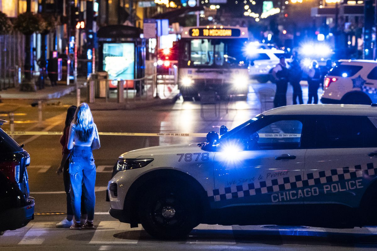 Passersby watch as Chicago police investigate Saturday night in the first block of East Washington Avenue in the Loop, where a CTA bus driver was physically attacked and then shot.