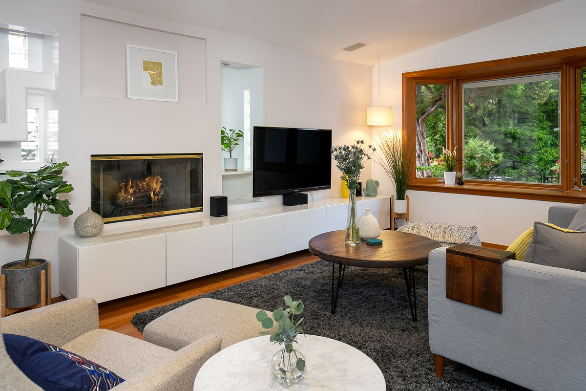 A room furnished with a sofa, an armchair, and a coffee table. A flatscreen TV is positioned on top of a cabinet