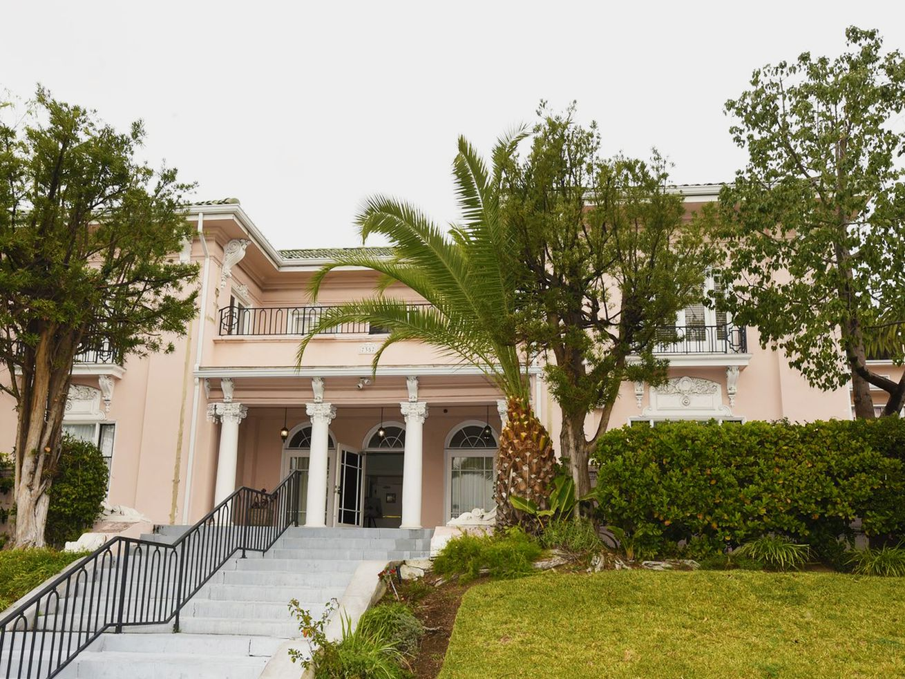 A decadent pink mansion fringed by palm trees sits atop a grassy hillside with a long staircase leading up to it.