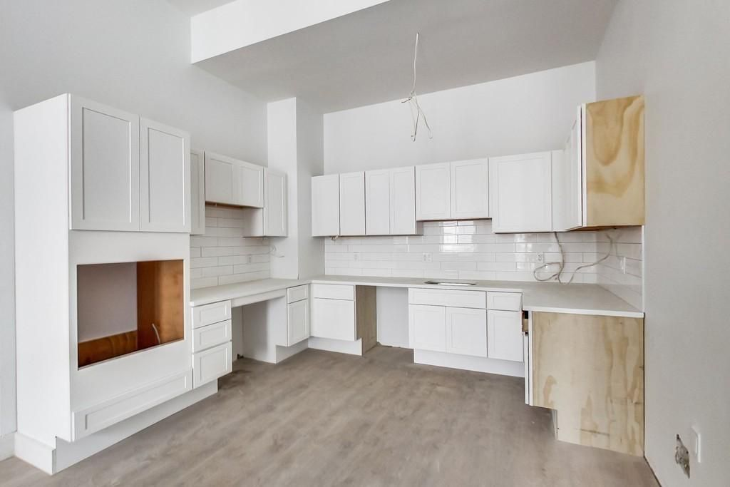 An open, empty, partially unfinished kitchen with lots of cabinetry.
