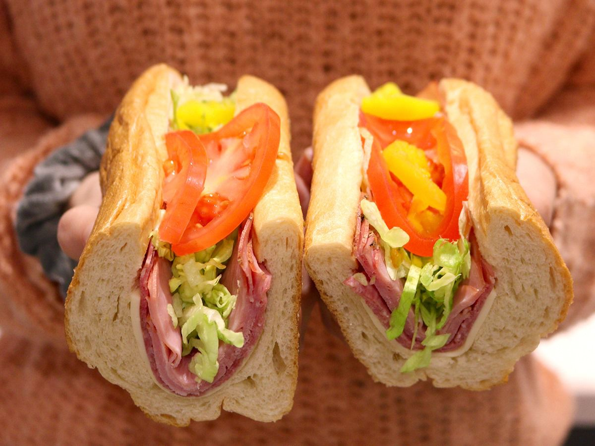 Person holding up an Italian hoagie cut in half.