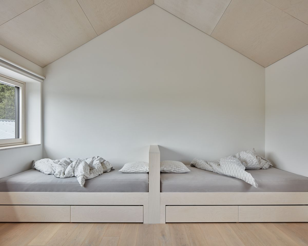 A children's bedroom with back-to-back twin beds with gray bedding.