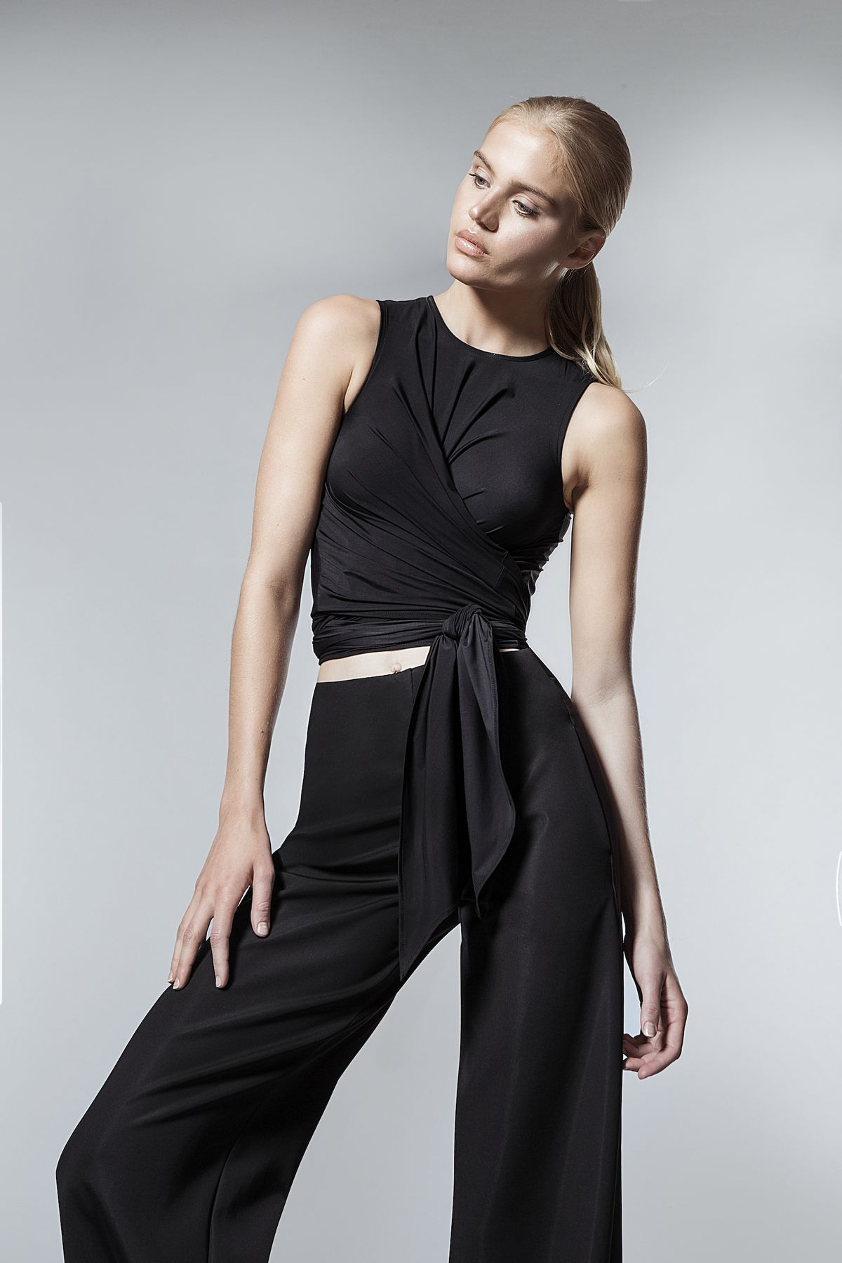 A model wearing black pants and a black tank top
