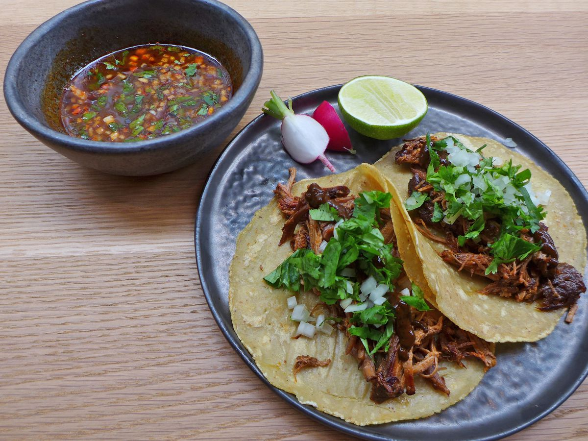 A pair of chopped meat tacos covered with chopped onions and cilantro, with a saucer of soup on the side.