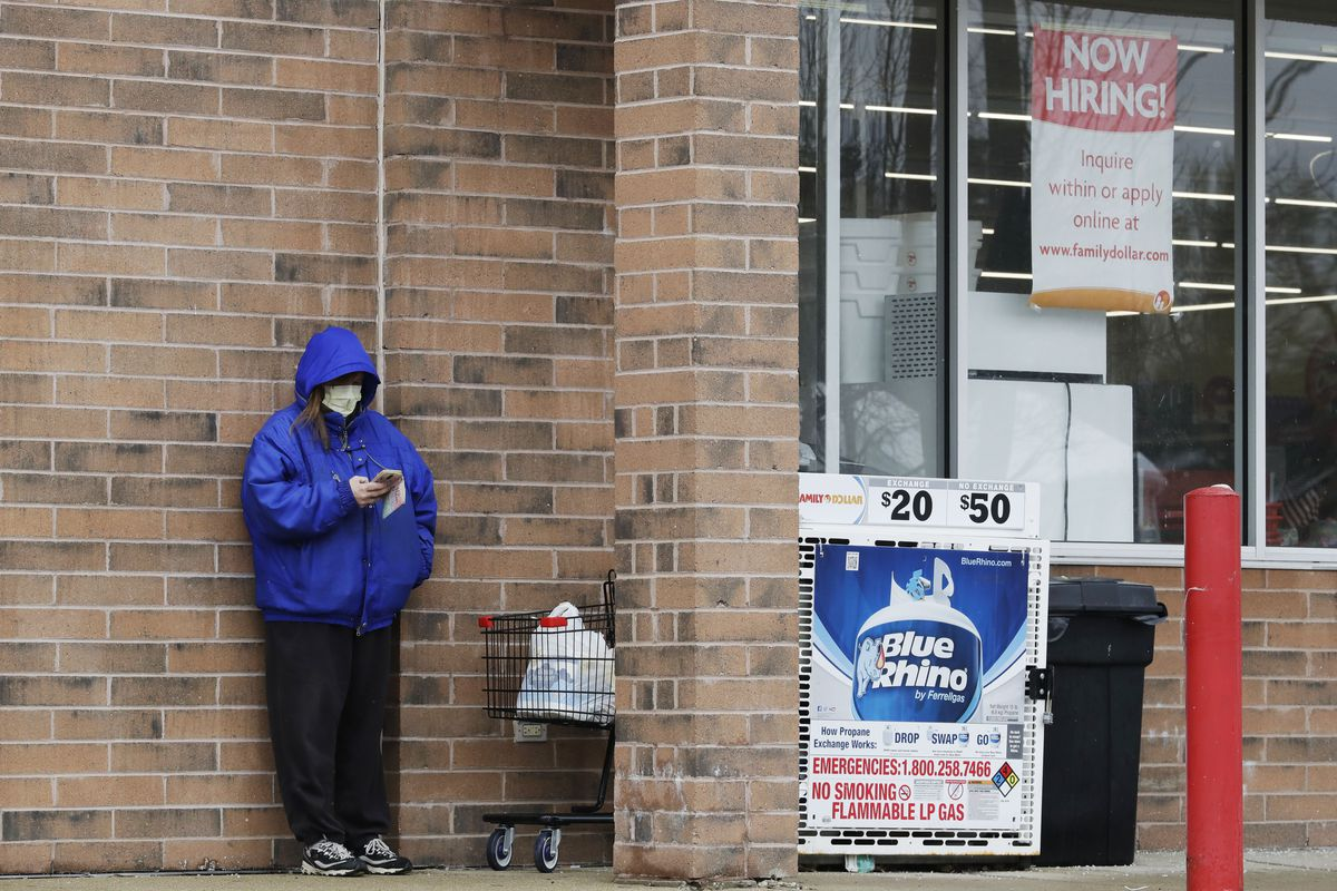 A woman checks her phone as a hiring sign shows at a Family Dollar store in Joliet.