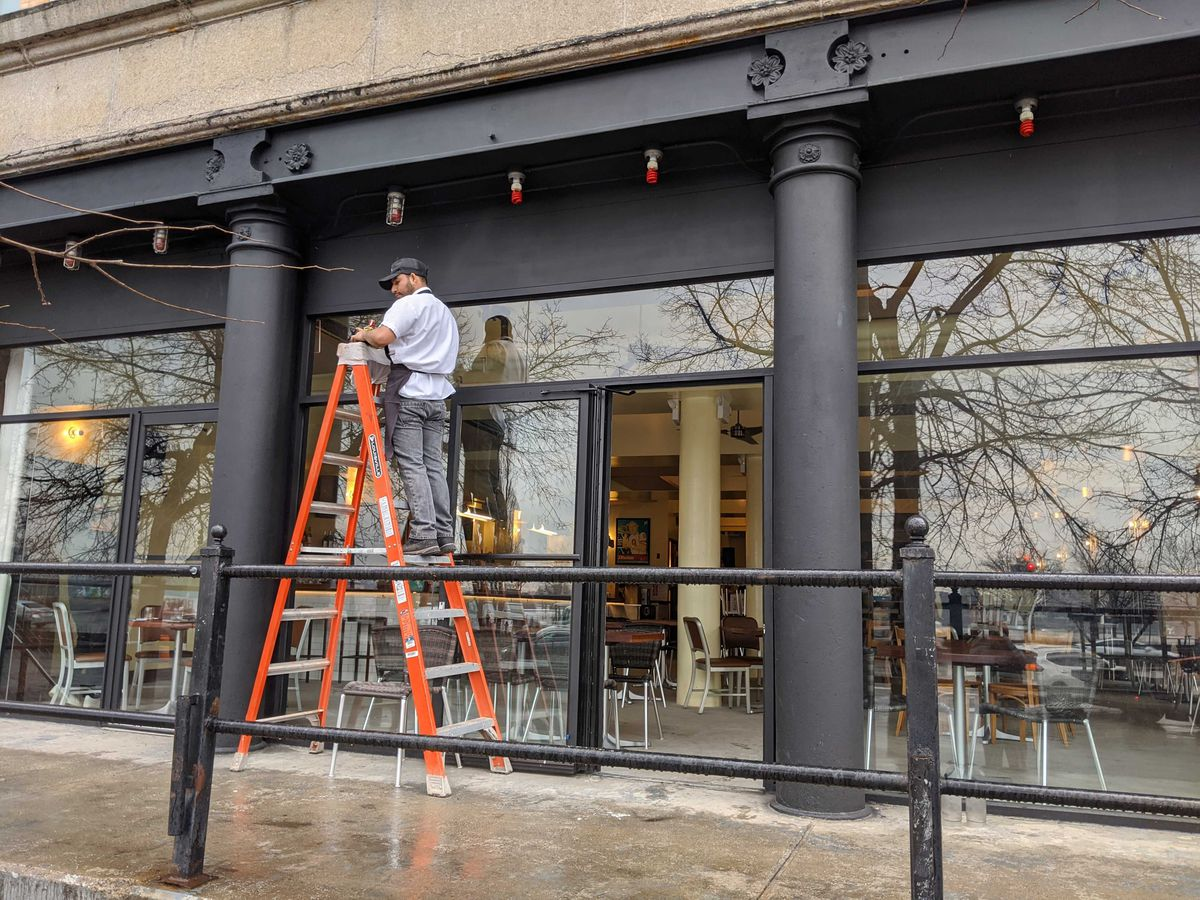 A man stands on an orange ladder in between slate gray columns on the side of a restaurant