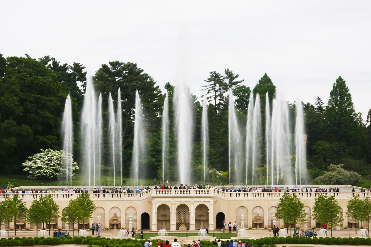 The exterior of Longwood Gardens. There is a tan building structure with columns. Above the building are various fountains and an outdoor viewing area full of people.