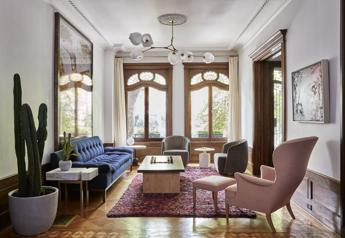 A living area. There is a blue couch, a coffee table, a pink arm chair with a pink footrest, and white end tables. Two windows are on the far wall. There are multiple large works of art hanging on the walls. A large cactus is in a planter.