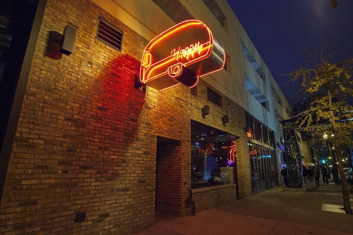 A neon sign hanging on a brick wall.