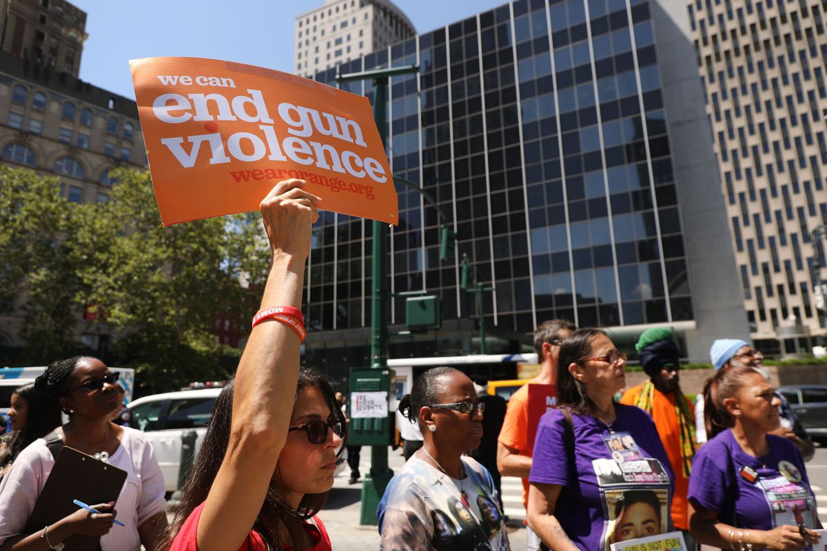 """A person at a protest holds up a sign that reads, """"End gun violence."""""""
