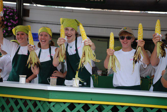 Five people inside the old corn roast booth all holding charred cobs up and grinning toothily