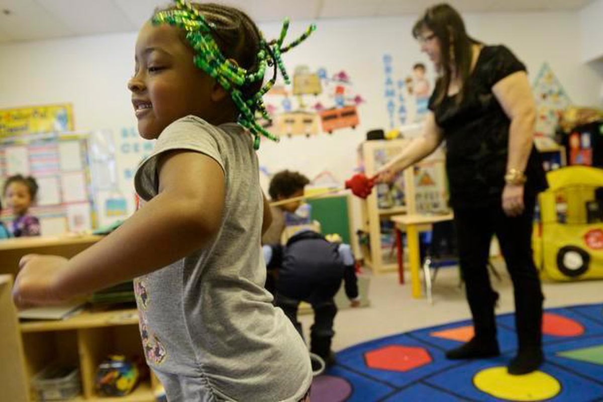 Zoe Johnson, 4, dances after walking through the limbo line in her Little Discoverers classroom at HOPE Center.