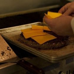 Tim Radigan arranges 10 slices of cheese on the burger.