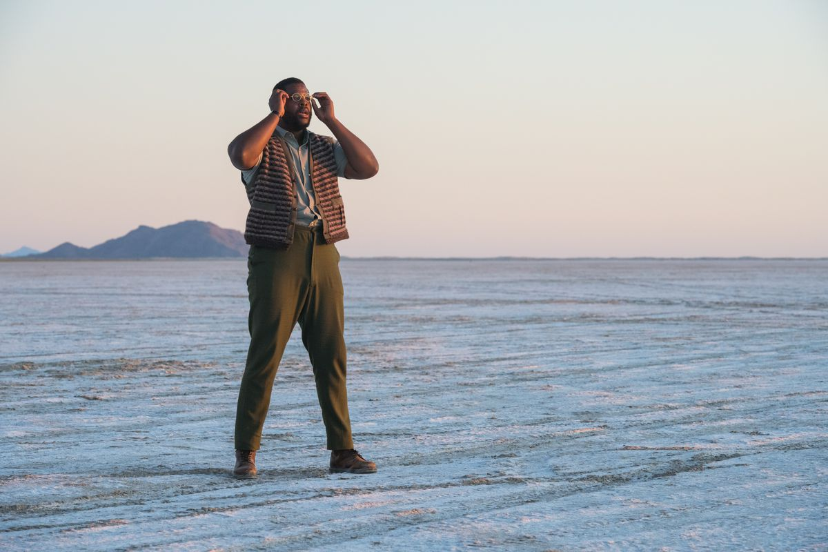 Black Panther's Winston Duke stands in the barren blue desert, clutching his glasses, in Nine Days