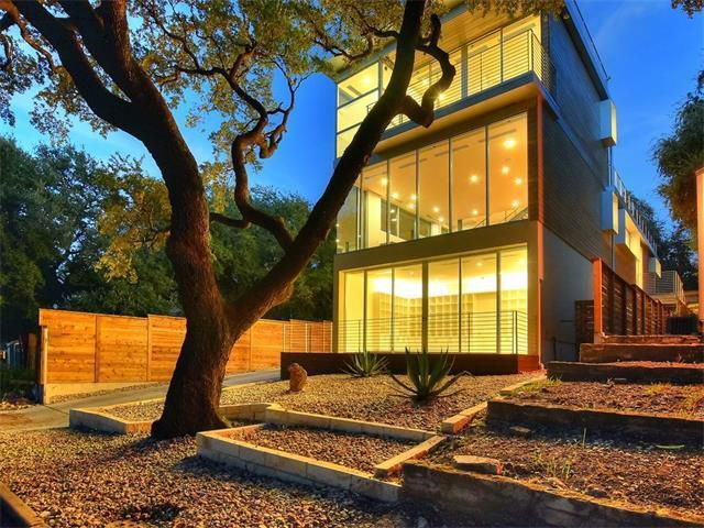 three stories of glass-wallled residence aglow with tree and terraced xeriscaping in front