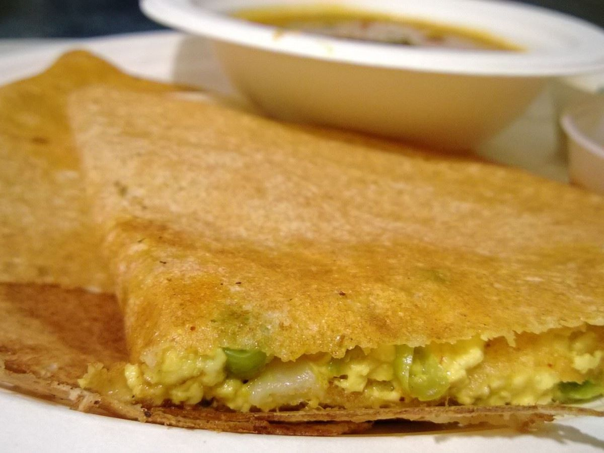 A closeup of a dosa stuffed with spiced potatoes and peas.