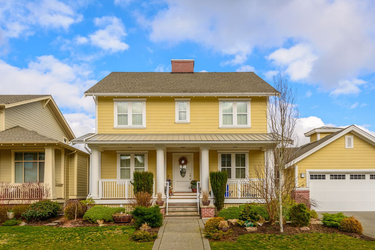 Yellow two-story house with covered porch and attached garage on the right.