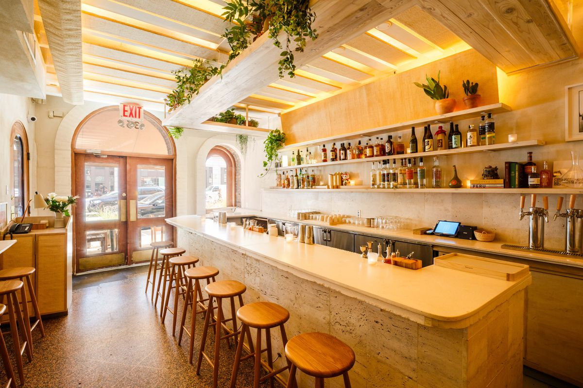 A warm, wood-accented bar with overhanging plants