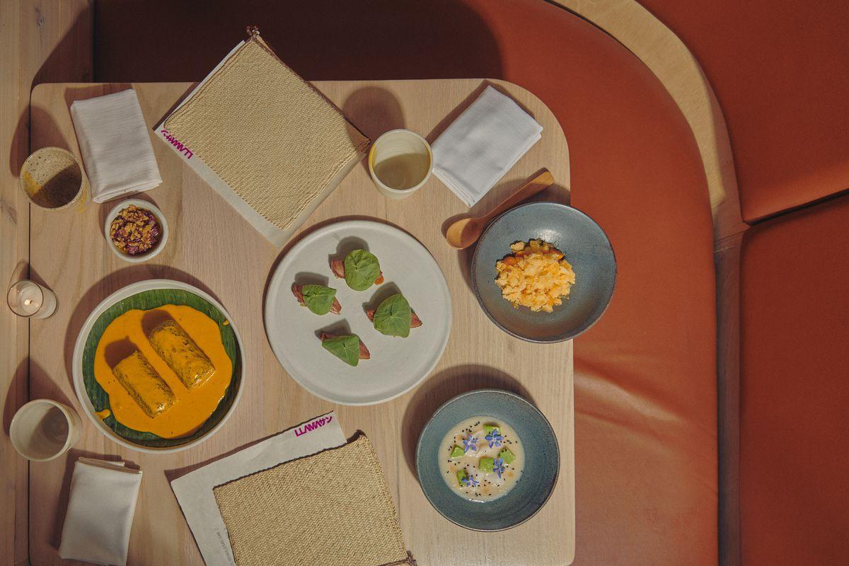 Chicken maki rolls, duck nigiri, scallops with cherimoya, and satsuma ice sit on a blonde table