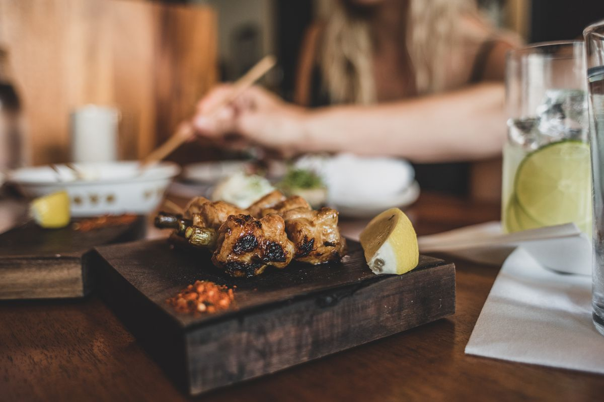 wood-grilled chicken skewers served on wood board with lemon and togarashi