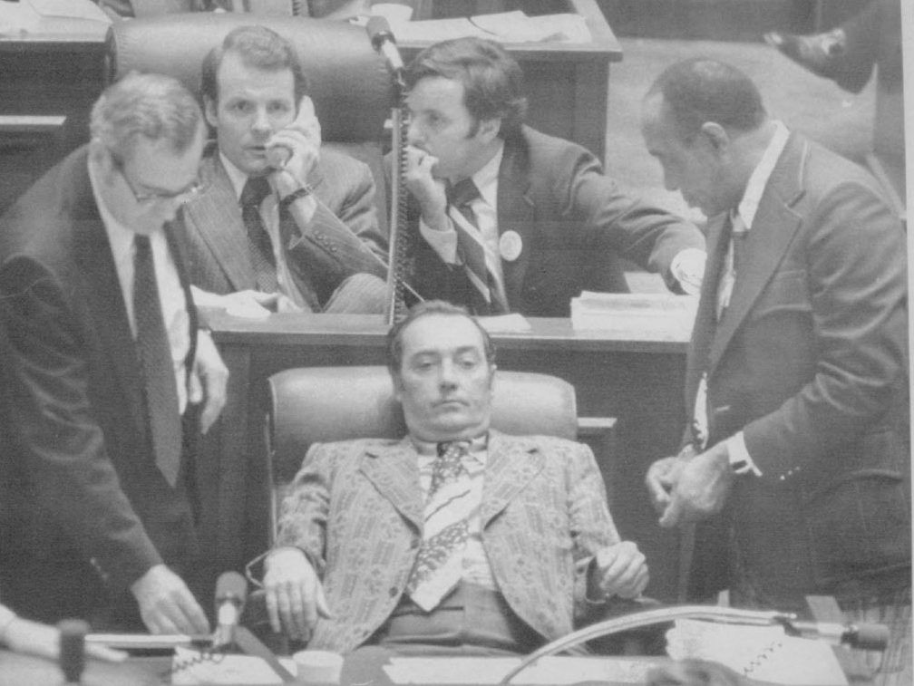 State Rep. Michael J. Madigan, top left, talks on the phone as state Sen. Richard M. Daley, kneels alongside during a meeting of Democratic leaders of both houses on the Illinois House of Representatives floor in Springfield in 1975. State Senate Presiden