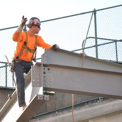 Steel worker directing the beam installation in the right-center field patio -