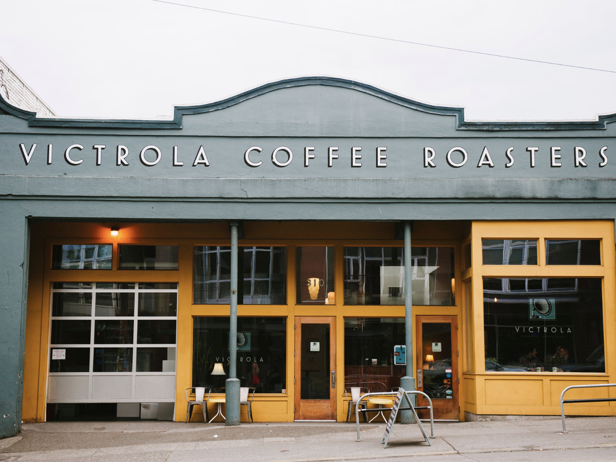 The exterior of Victrola Coffee Roasters, showing the shop's name across the top against a light gray background.