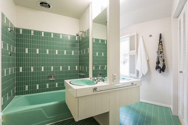 An original midcentry modern bath has teal tile, a teal tub, and two back-to-back vanities.