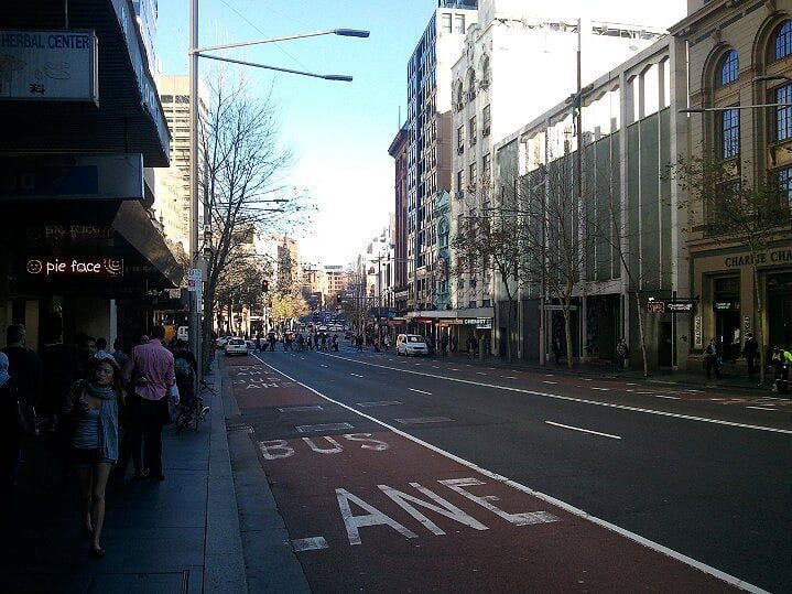 A main street in Sydney Australia with people all around.