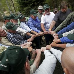 Cancer patients and volunteers gather in a circle during the closing ceremony of the Reel Recovery cancer retreat at Falcon's Ledge fishing lodge near Altamont.