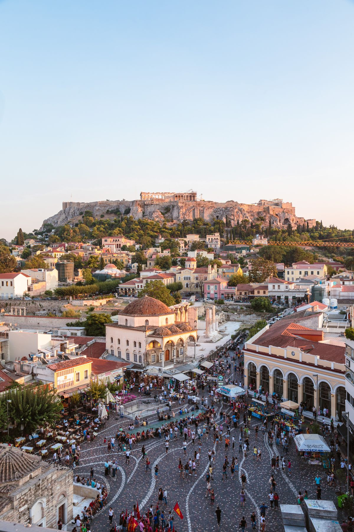 An aerial view of Athens, Greece. There is a pedestrian plaza surrounded by various buildings. In the distance is a mountain with historic buildings.