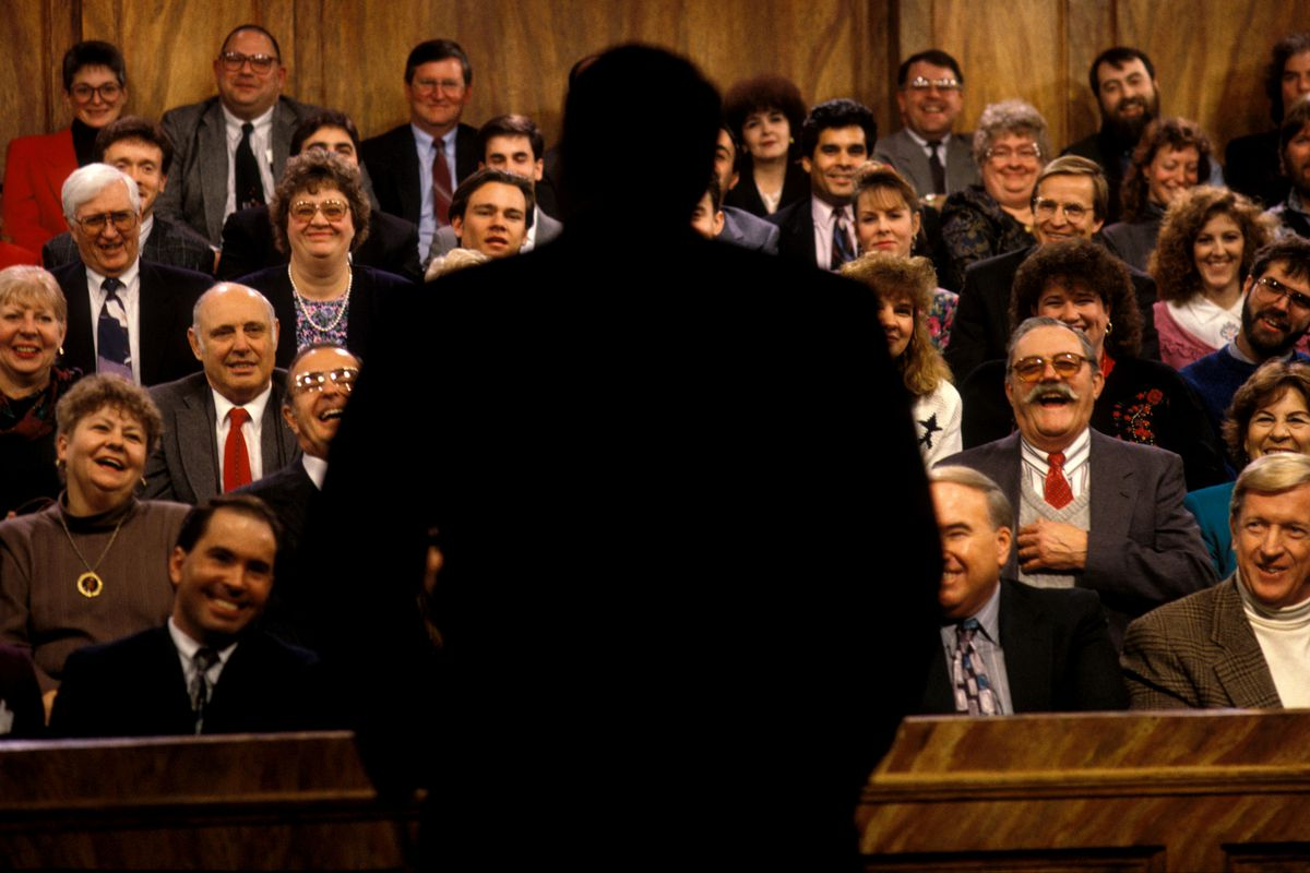 Rush Limbaugh from behind in silhouette, with a laughing audience facing him.