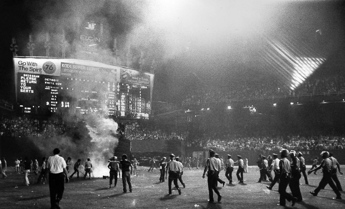 """Police sweep the field at Comiskey Park amid flames and smoke in center field during the infamous WLUP-FM """"Disco Demolition"""" stunt in 1979. 