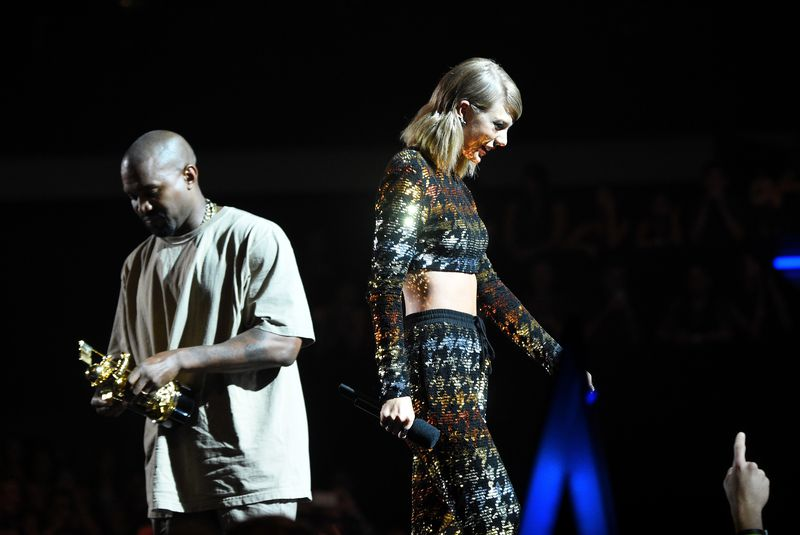 Kanye and Taylor are back-to-back, both looking down, silhouetted against a dark backdrop.