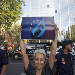 A demonstrator holds a altered EEC poster outside the EEC headquarters during a protest against the visit by German Chancellor Angela Merkel in Madrid, Thursday Sept. 6, 2012.  Merkel and Rajoy met for talks on Spain's progress with crushing austerity measures. The government, which is struggling to pay punishingly high interest rates to raise money, is under pressure to accept a sovereign bailout.